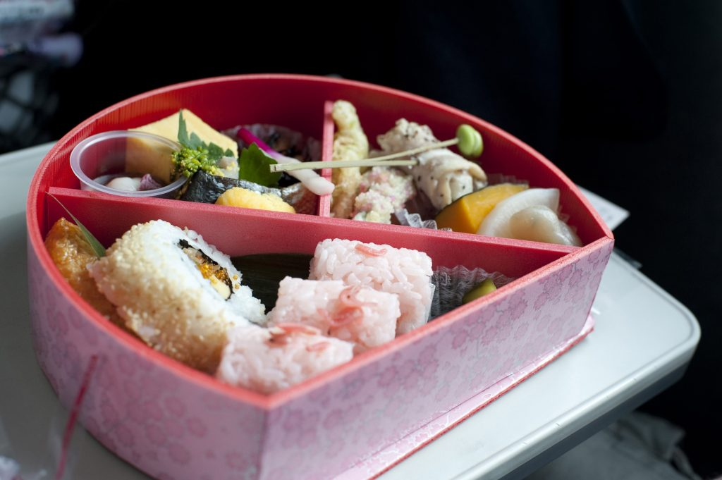 Serving of food inside a bento box, a lacquered container with internal divisions to house a complete traditional Japanese meal